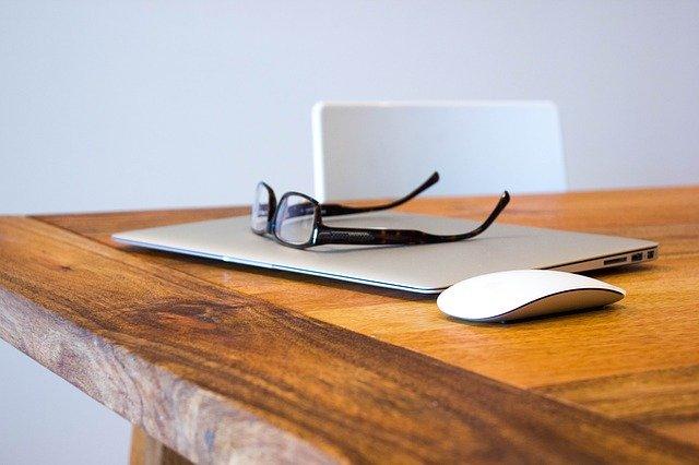 テーブルの上のノートPCとめがね